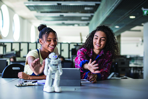 Girls program a robot.