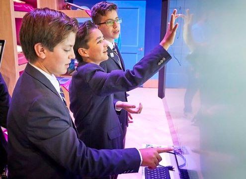Three boys use an electronic whiteboard