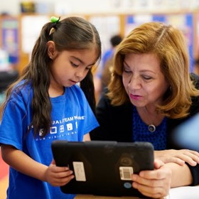 A girl and her teacher looking at an iPad