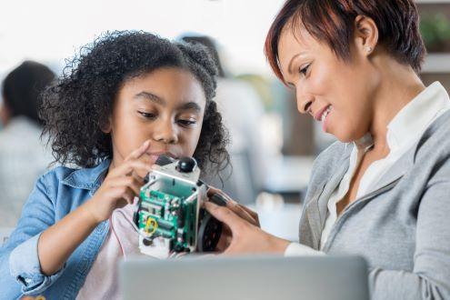 A teacher helps a student program a robot.