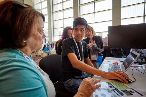 A student helps a teacher at the ISTE Conference & Expo.