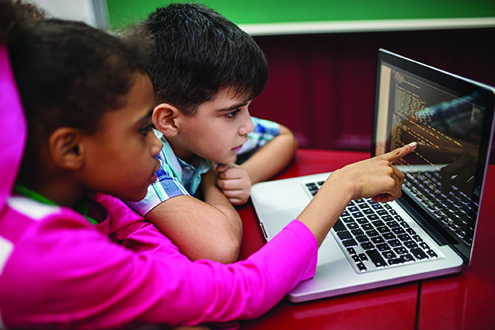 Children work together on a computer