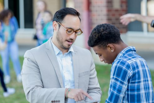 School principal helps student with iPad