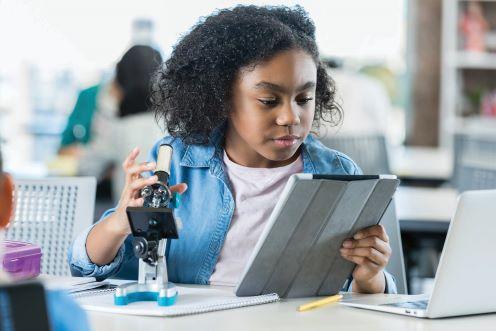 A girl looks through a microscope
