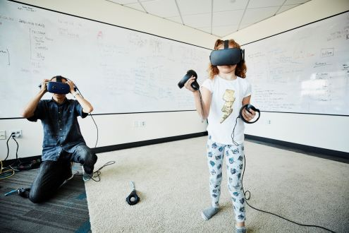 A child wearing an augmented reality headset while an adult looks on