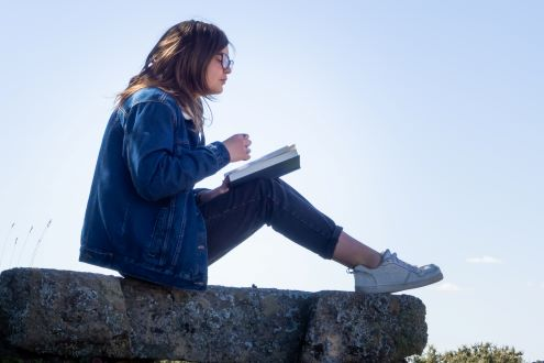 A student reads a book outside to take a break from her digital device.