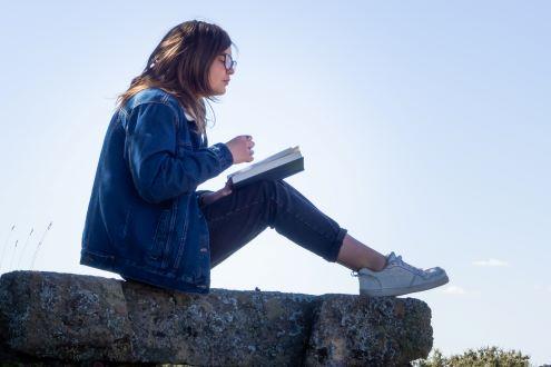 Una estudiante lee un libro afuera para tomar un descanso de su dispositivo digital.