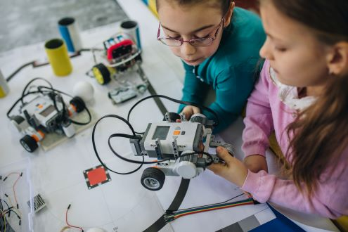 Two girls code a robotic vehicle