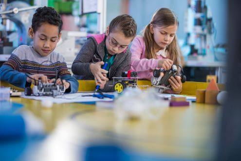 three children work in school makerspace