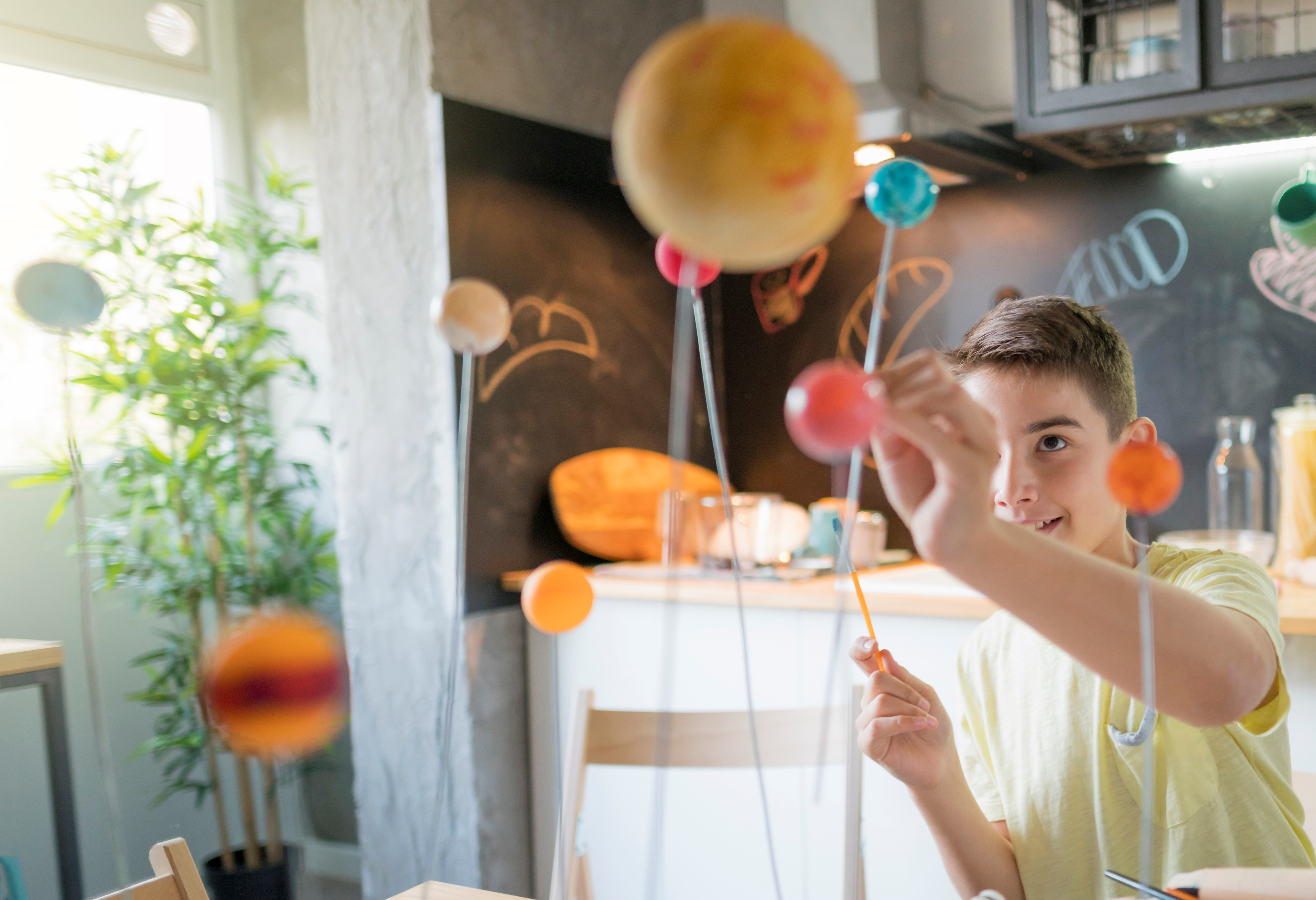 A student examines a solar system model