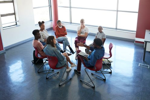 A group of educators in a circle having a discussion.