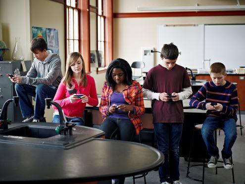 5 estudiantes usan teléfonos inteligentes en la clase de ciencias