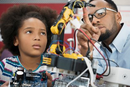A student works on a robotics project with her teacher