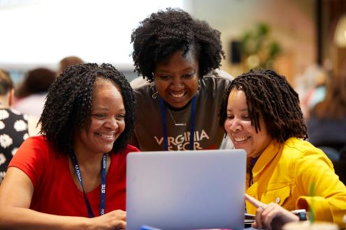 3 edtech coaches smile as they look at a laptop screen
