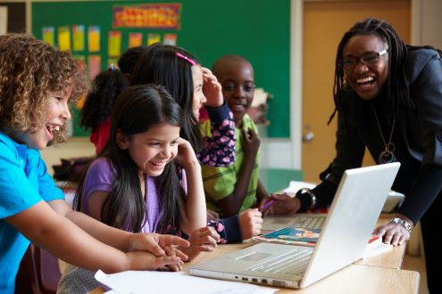 Two children smile while looking at a laptop while a smiling teacher looks on.