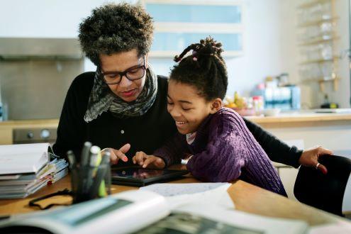 Una madre y su hija usan un teléfono celular