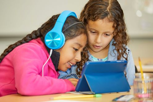 two students listen to a story on an iPad