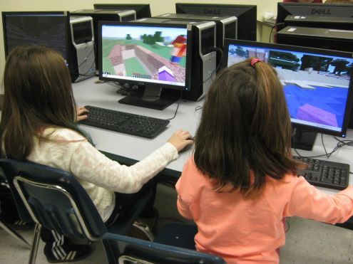 Two girls playing Minecraft in school
