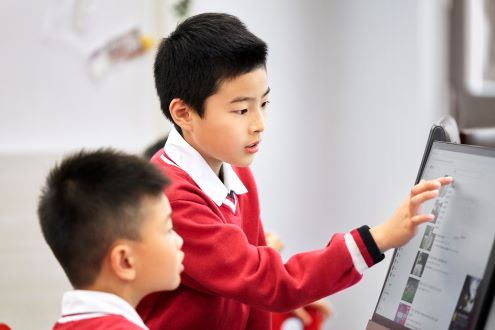 Two boys in china work on a computer