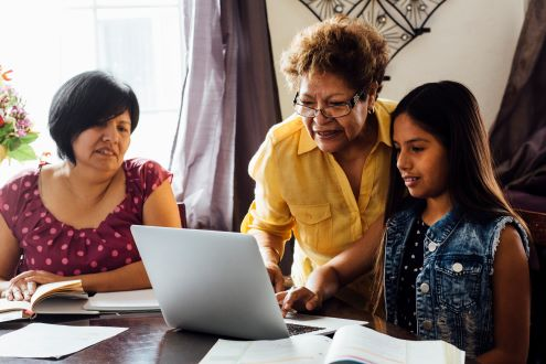 A student is doing her homework while a grandmother and mother help