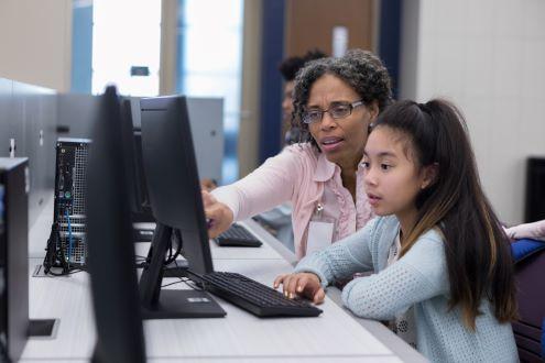 A teacher and a student working at a desktop computer