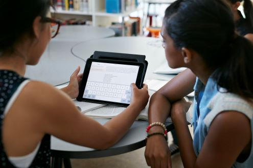 Two students read on a digital tablet
