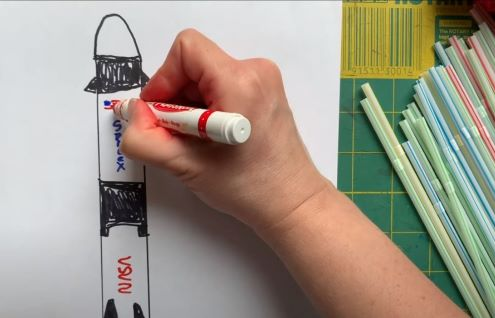 A child's hand drawing a rocket.