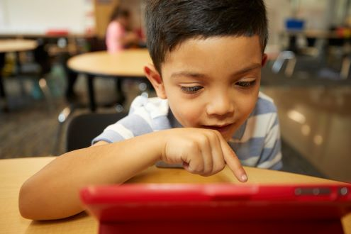 a young boy uses a tablet in school
