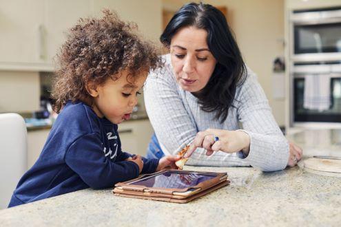 A parent helps a child use an iPad