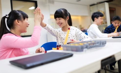 Two student celebrate with a high five