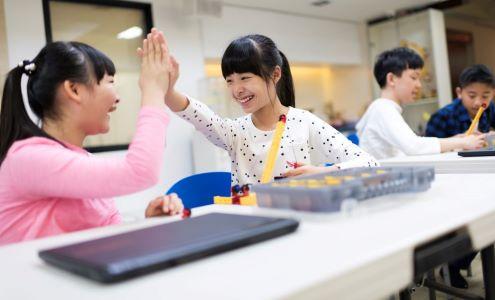 Dos estudiantes celebran chocando los cinco