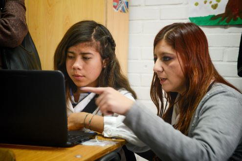 A teacher helps a students with computational thinking