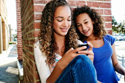 two girls smile while looking at phone screen