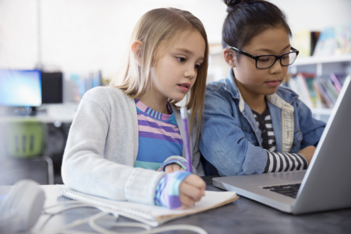 Two elementary school girls coding with a laptop