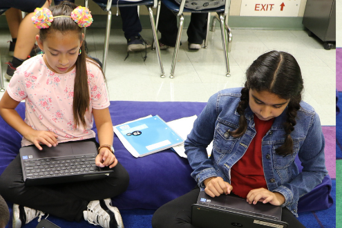 two girls sitting on classroom floor with laptops working on coding projects
