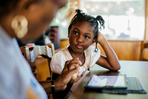 a girl with an iPad listens intently to her parent