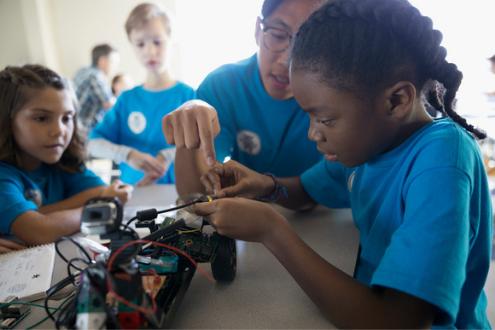 Three children build a robotic car together