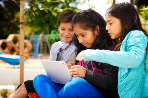 Tres estudiantes alrededor de una computadora portátil trabajando en un proyecto de codificación.