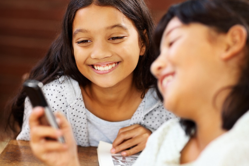 two girls laughing at something on a phone