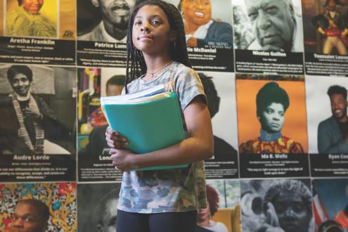una niña se para frente a una pared celebrando a los líderes negros
