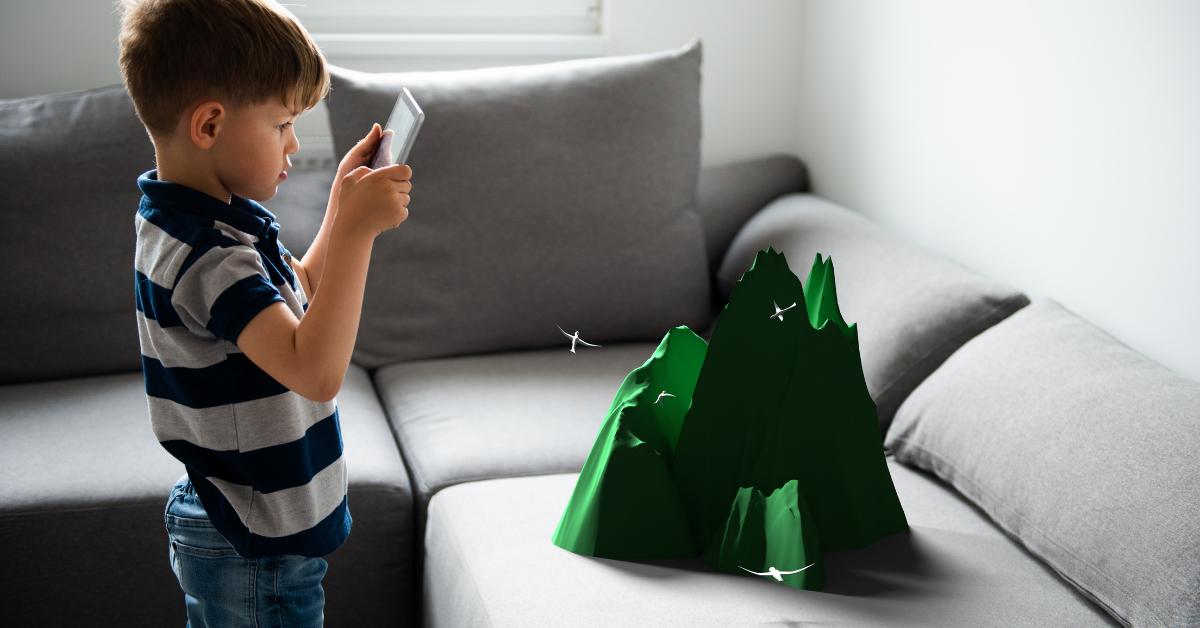 A young boy uses an AR app to see a 3D image of a mountain
