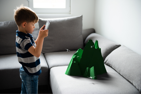 A young boy uses an AR app to see a 3D image of a mountain