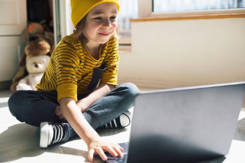 una niña trabaja en una computadora portátil en el piso de su casa