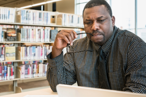 An educator concentrates while looking at his laptop