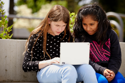 Two girls work on a laptop at school