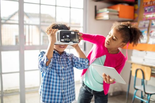 A girl helps a boy with a VR headset