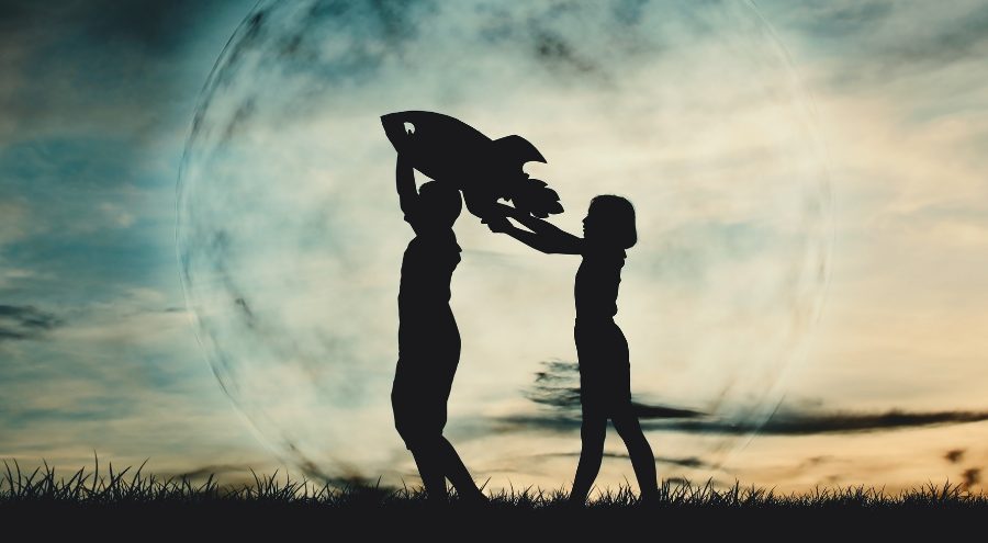 A silhouette of children playing with toy rocket.