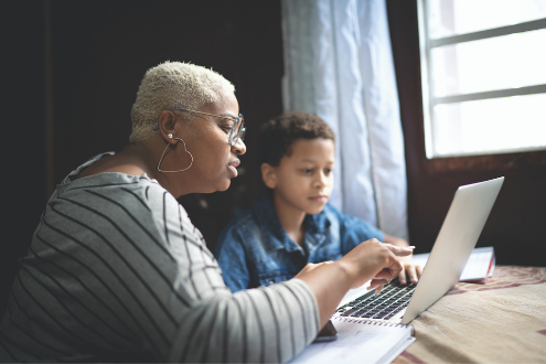 A woman helps a child read something on a laptop