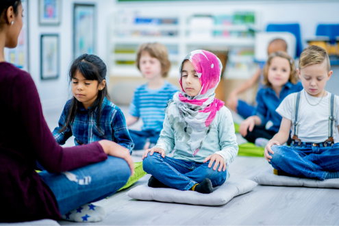 Young students in a classroom meditate