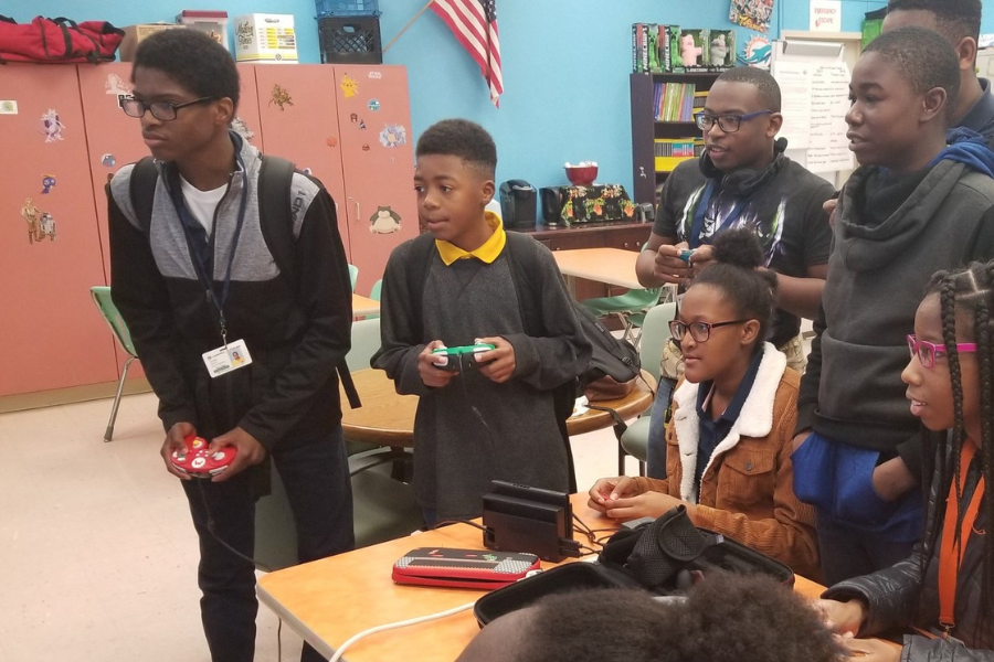 A group of children in a classroom play a video game